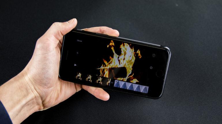 Telefon w ręce z odpaloną aplikacją do montowania filmów na IOS iMovie